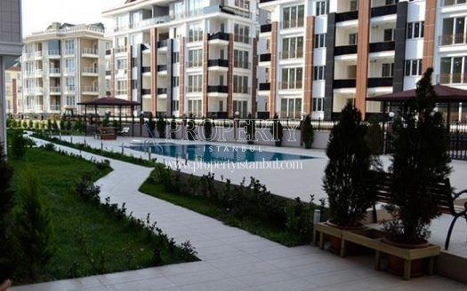 Outdoor swimming pool among the buildings in Pinartepe Residenceidence compound